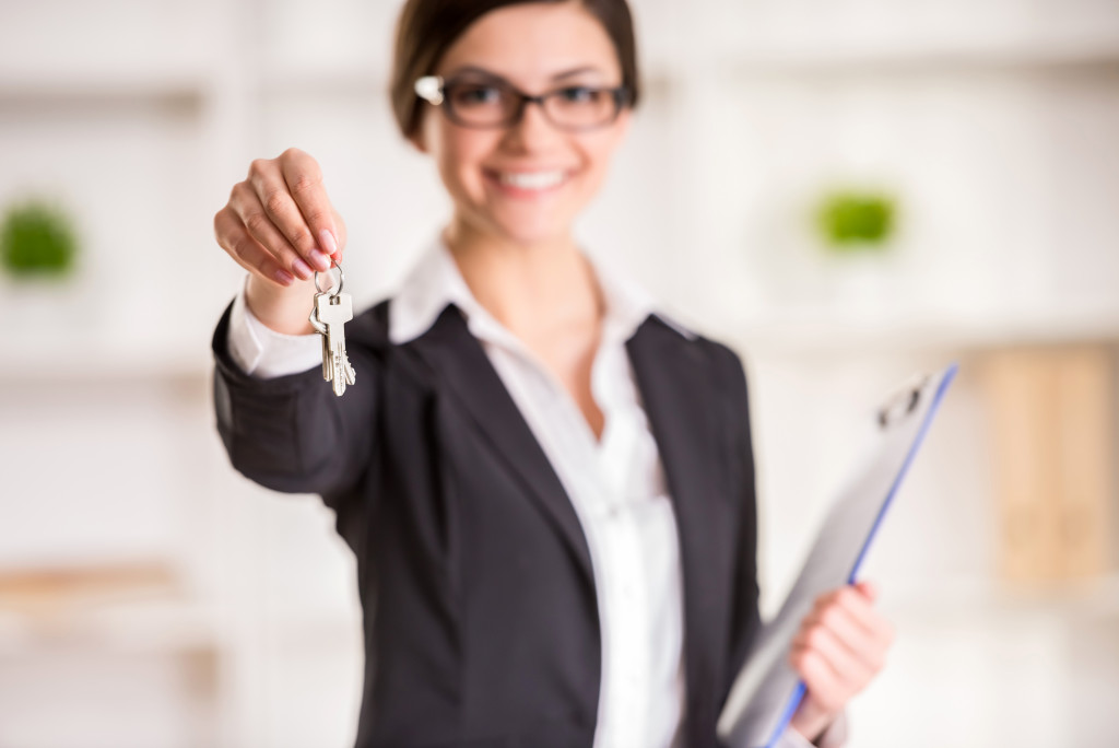 woman holding keys to a house